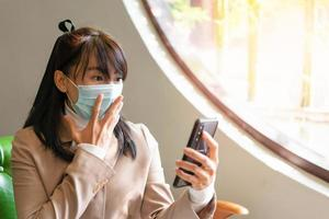 Business woman wearing surgical mask and using smartphone photo