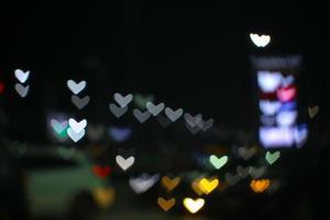 arco iris y desenfoque en forma de corazón día de amor luz de noche colorida en la calle foto