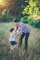 Daddy hugging her little boy. Family walking in the field. Outdoors. photo