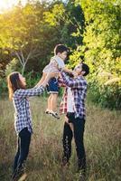 familia joven feliz pasar tiempo juntos afuera. concepto de amor familiar foto