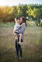 mamá abrazando a su pequeño. familia caminando en el campo. al aire libre. foto