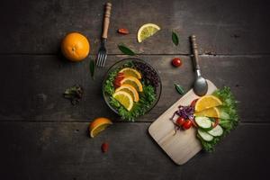 Ensalada de verduras frescas con rodajas de naranja y tomate en la sartén. foto