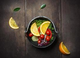 Fresh vegetable salad with orange on the pan over wooden background photo