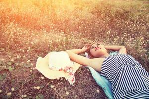 Young sexy woman lying in grass nearing her hat look into the sky. photo