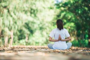 Young asian woman doing yoga in the morning at the park. photo