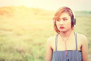 beautiful sexy woman standing listening sad music in the flower fields photo