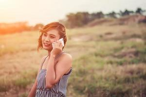 hermosa mujer sexy de pie hablando por teléfono en la hierba. foto