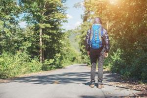 Rear of hiker man walking on the rural road. Holiday tourism concept. photo