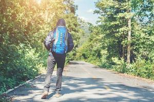 Hiker man walking on the rural road. Holiday tourism concept. photo