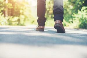 pies de hombre caminando por el camino rural. concepto de turismo de vacaciones. foto