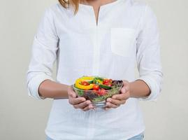 Close-up of womans hands holding bowl with fresh salad photo