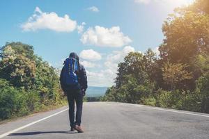 hombre caminante caminando por el camino rural. concepto de turismo de vacaciones. foto