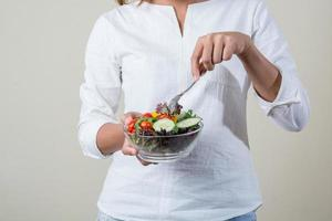 Close-up of woman hands holding eating fresh vegetable salad photo