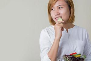 Bella mujer de pie sosteniendo un tazón de ensalada comiendo algunas verduras foto