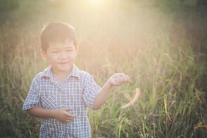 Happy little asian boy playing outdoors. Cute asian. boy on field. photo