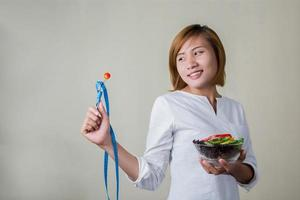 Woman standing holding bowl of salad looking at fork dipping tomato. photo