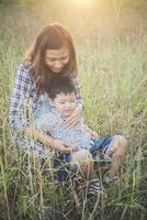 Mommy hugging her little boy. Family walking in the field. Outdoors. photo