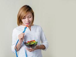 Woman holding fork with fresh mixed vegetables and measuring tape. photo