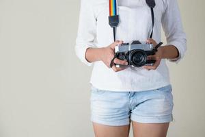 Beautiful young woman photographer holding retro camera photo