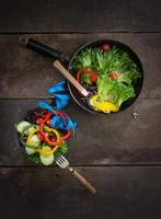 Fresh vegetables salad on  bowl with measuring  wooden background. photo