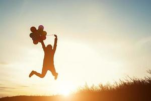 young woman with balloons jumping outdoor photo