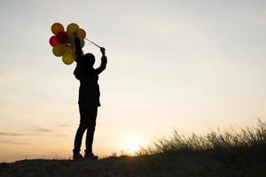 silueta, de, mujer joven, tenencia, colorido, de, globos, con, ocaso foto