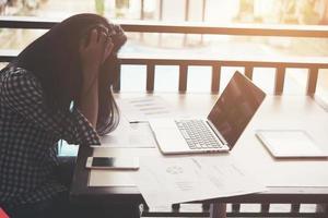 Manos de mujer frustrada mientras está sentada en su lugar de trabajo en la oficina. foto