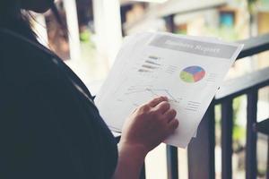 Manos de mujer financiera apuntando a notas del gráfico de finanzas mientras trabaja foto