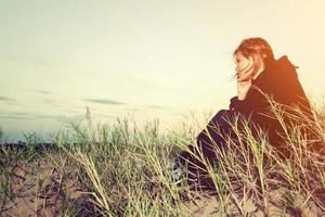 triste niña sentada sola en un césped al aire libre, tristeza. soledad foto