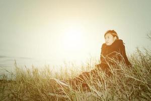 Triste joven sentada en la hierba sintiéndose tan triste y soledad foto