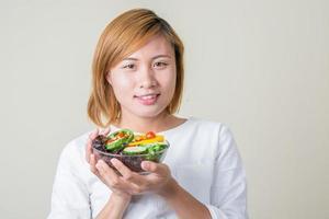 Beautiful woman holding bowl of fresh vegetable salad smiles at camera photo