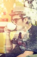 Young man drinking coffee inside cafe with sunrise photo