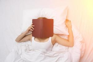 young woman sleeping on the bed after  with face covered by the book. photo