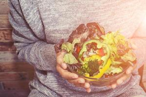 hands of beautiful woman holding big bowl of fresh veggie salad. photo