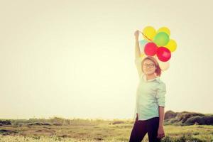 Mujer de pie sosteniendo coloridos globos en el campo y smiley foto