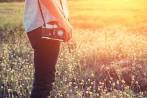 Beautiful young woman photographer holding retro camera in summer. photo