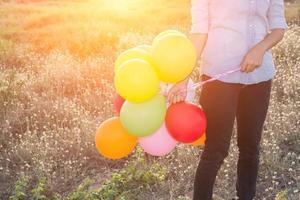 Manos de mujer hipster sosteniendo globos multicolores en los prados foto