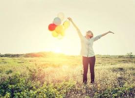 mujer de pie sosteniendo globos en el campo mirando al cielo. foto