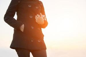 Manos de mujer llevando cámara retro con abrigo negro en el parque foto
