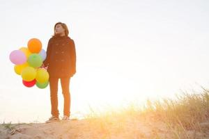 young woman holding balloons wearing black coat in the feeling sadly. photo