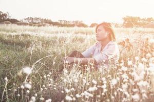 Hermosa joven inconformista pensativa mujer sentada en los prados foto