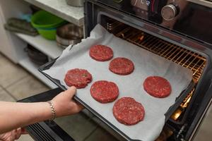 Putting hamburgers in the oven photo