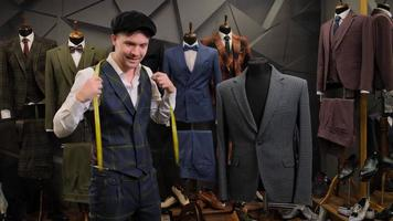 Tailor posing with suits photo