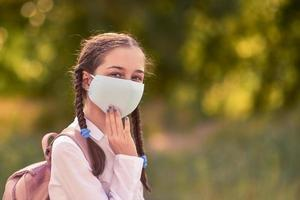 Back to school. Girl in protective mask. photo