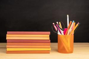 Pile of books and office supplies on wooden table. Copy space photo