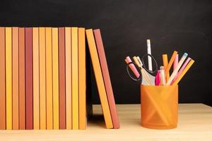 Group of books and pencils on wooden table. Copy space photo