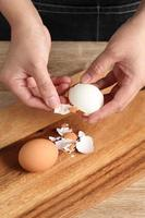 Chef peeling boiled egg on wooden cutting board photo