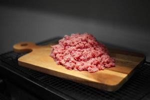 Minced meat on cutting board in kitchen photo