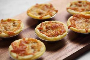 Mini pie from meat and mushrooms in wooden tray photo