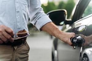 el hombre mayor abre la puerta de su auto con acceso sin llave. foto